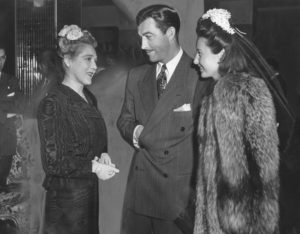 "Photograph caption dated April 2, 1943 reads, ""Hollywood was charmed by China's First Lady. Among those caught by her beauty and magnetism were, left to right, Mary Pickford, Robert Taylor and Barbara Stanwyck. The Missimo walked casually about the Gold Room as she visited with the stars."""